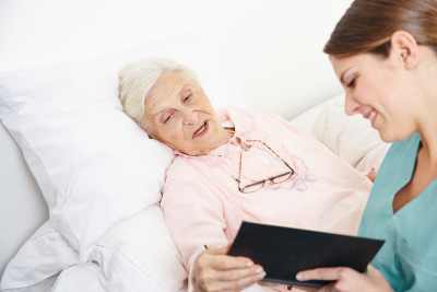 nurse reading book to senior citizen woman in bed